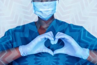 A Covid-19 frontline worker making a heart-shaped sign