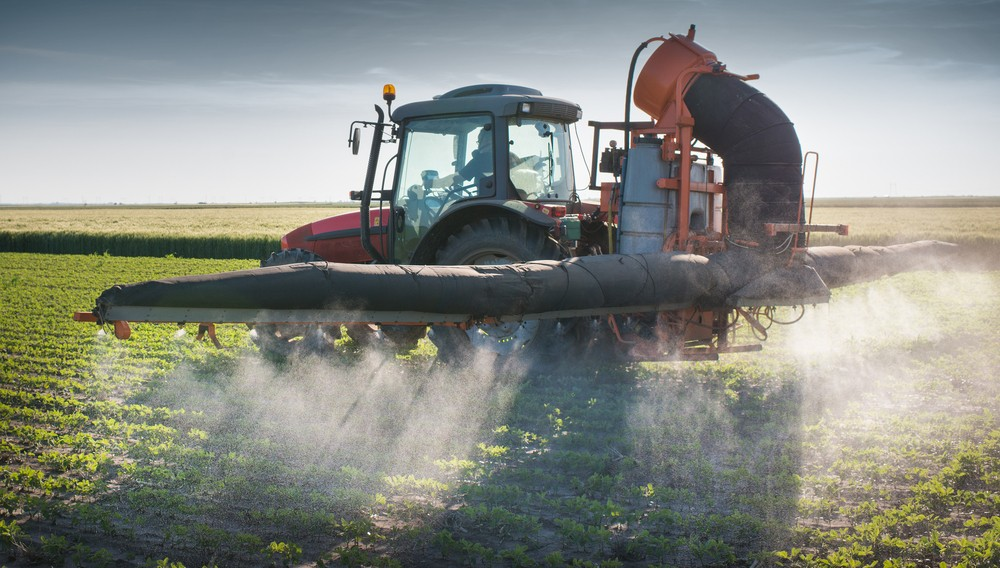 Photo: Tractor spraying pesticides on soy bean crop. Via: Fotokostic   Shutterstock.